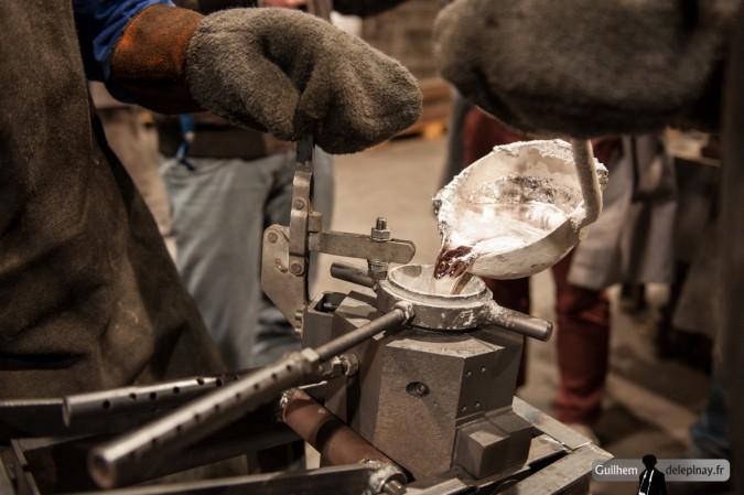 reportage fonderie : la coulée au renversé - L'aluminium est versé depuis la louche dans l'orifice du moule, penché à 30°C pour améliorer l'écoulement du métal.